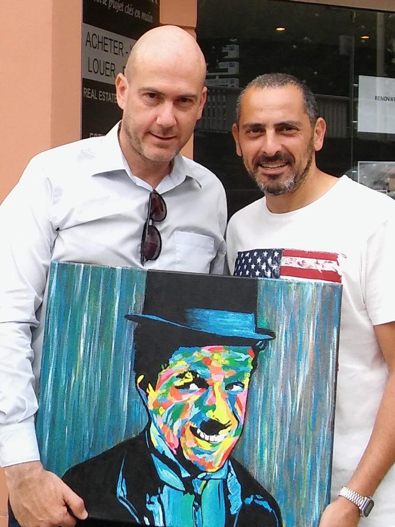 Lionel Cohen et un client posant avec le portrait de Charlie Chaplin