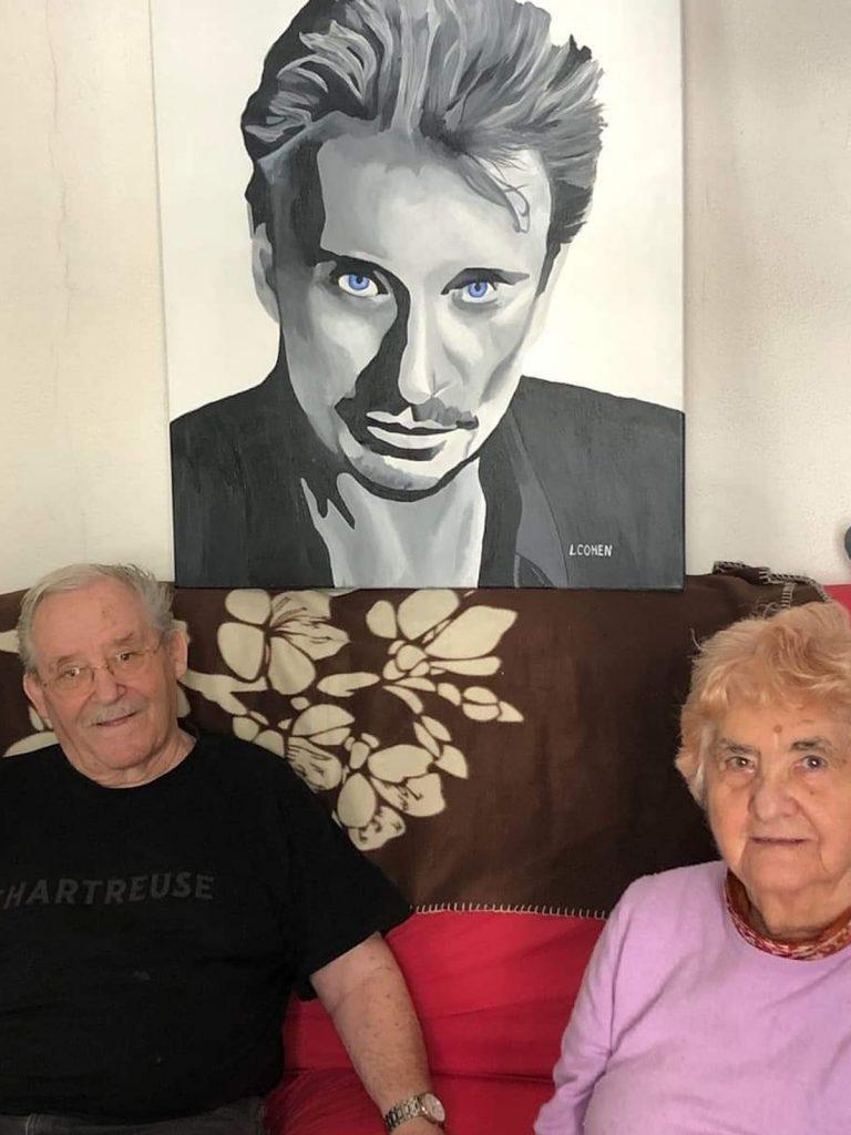 Un couple posant avec le portrait de Johnny Hallyday