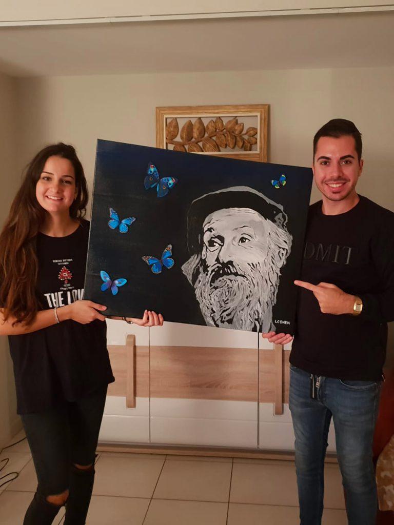 Deux jeunes gens posant avec un portrait du rabbi dans leur salon
