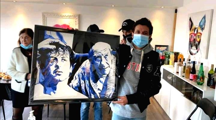 Client de Lionel Cohen posant avec le portrait de Rocky et Rabbi