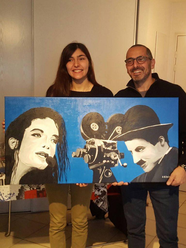 Lionel Cohen remettant un tableau portrait de Mickael Jackson et Charlie Chaplin
