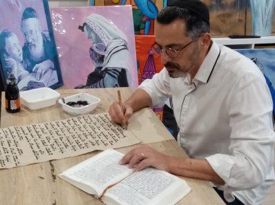 l'artiste peintre Lionel Cohen entrain d'écrire sur une toile de jute un texte hébraïque